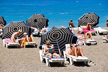 People sunbathing on sunloungers at main beach, Rhodes Town, Rhodes, Greece