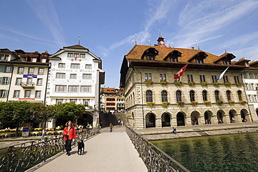 Woman with dog walking over bridge Rathaussteg, city hall at Rathausquai in background, River Reuss, Lucerne, Canton Lucerne, Switzerland