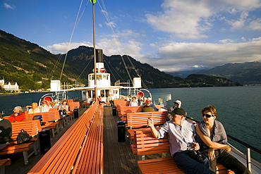 Passengers sitting on deck of a paddle wheel steamer, Lake Lucerne, Canton of Lucerne, Switzerland