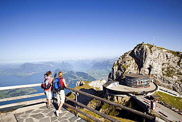 Two female hikers standing on vantage point looking to Hotel Bellevue in front of mount Esel (2118 m), panoramic view over Lake Lucerne, Pilatus (2132 m), Pilatus Kulm, Canton of Obwalden, Switzerland