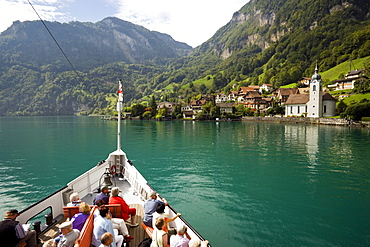 Passengers sitting on deck of a paddle wheel steamer, arriving Bauen, Lake Urnersee, part of Lake Lucerne, Bauen, Canton of Uri, Switzerland