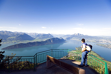 Man standing on vantage point Kaenzli, mount Rigi (1797 m, Queen of the Mountains) and looking over Lake Lucerne with Weggis, mount Buergenstock and mount Pilatus (2132 M), Rigi Kaltbad, Canton of Schwyz, Switzerland