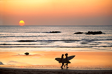Surfer on Playa Coco at sunset, Costa Rica