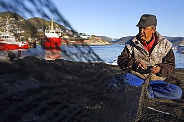 An eskimo, inuit at Qaqortoq (former Julianehab), repares a fishing net, South Greenland.
