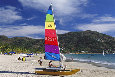 A boat, catamaran, on the beach at Playa la ropa, Zihuatanejo, Guerrero, Mexico, America