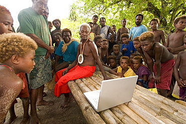 Traditional Tribe looking at Apple computer, New Ireland, Papua New Guinea, Oceania