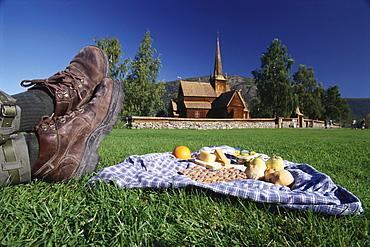 Man enjoying a Norwegan picknick at a church, Lom, Oppland, Norway