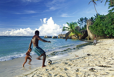 Seychellois playing football on the beach, Anse Source d'Argent, La Digue, Seychelles