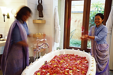 Women filling a bath with flower petals, Bathroom, Relaxation, Hotel Oberoi, Holiday, Mauritius, Africa