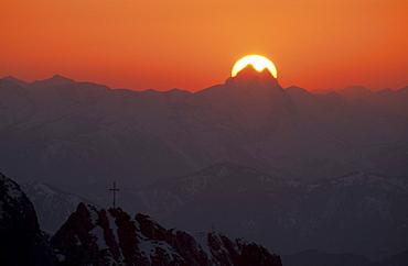 sun behind summit of Guffert with pinnacles with crosses on summit in foreground, Kaiser range, Tyrol, Austria