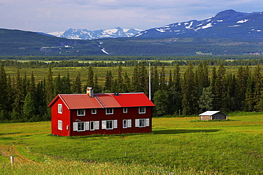 Red wooden house and view at snowcovered mountains near Klocka at the Annsjoen, Jaemtland, northern Sweden