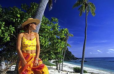Woman on a sandy beach looking out to sea, Navadra Island, Mamanuca group, Fiji, South Sea