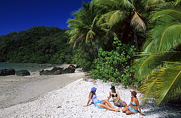 Three young girls sitting on the sandy beach, Muggy Beach, Dunk Island, Great Barrier Reef, Australia