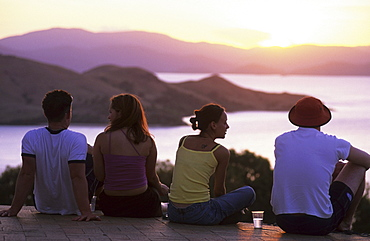 Four young people, couples enjoying the sunset from One Tree Hill on Hamilton Island, Whitsunday Islands, Great Barrier Reef, Australia