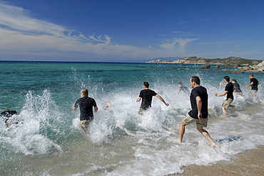 A group of men running into the sea, Adventure competition, North West coast, near Rena Majore, Sardegna, Sardinia, Italy, Europe, mr