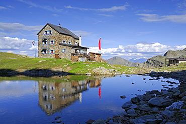 hut Flaggerschartenhuette with reflections in a lake, Marburg-Siegener Huette, Rifugio Forcella di Vallaga, Sarntal range, South Tyrol, Alta Badia, Italy