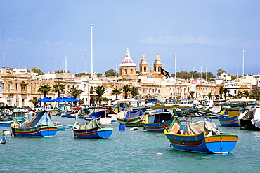 Boats at harbour in front of the church of Marsaxlokk, Malta, Europe