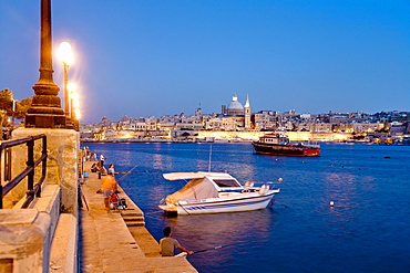 Anglers sitting on the promenade in the evening, view at the town of Valletta, Sliema, Malta, Europe