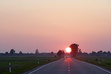 Sunset over country road in the district of Telsiai, Lithuania