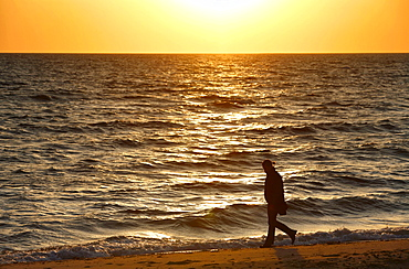 A woman walking on the beach at sunset, Wellfleet Harbor sunset, Cape Cod, Massachusetts, USA