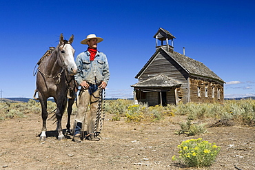 cowboy with horse at old schoolhouse, wildwest, Oregon, USA