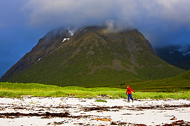 A woman walking along the beach in rainclothes, Hadselsand, Lofoten, Norway