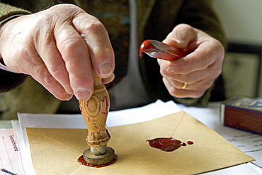 Notary fixes a seal on a document, last will and testament, inheritance seal, sealing wax