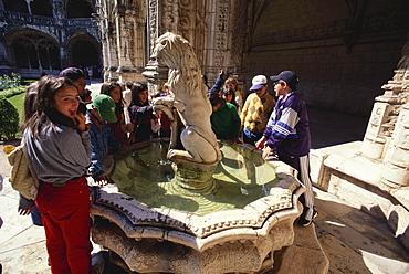 A group of children standing near a fountain, Cloister, Mosteiro dos Jeronimos, Hieronymites Monastery, Belem, Lisbon, Portugal