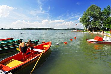 Two children fishing on rowing boat at beach of lake Simssee, Chiemgau, Upper Bavaria, Bavaria, Germany
