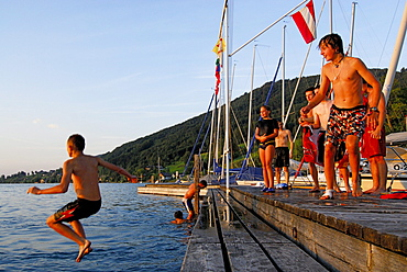 young men diving from landing stage, lake Attersee, Salzkammergut, Salzburg, Austria