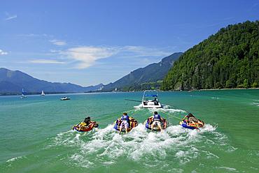 four young women and men tube riding behind motor boat, lake Abersee, lake Wolfgangsee, Salzkammergut, Salzburg, Austria