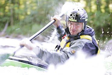 Man, Kayak guide, in a kayak, kayak weekend for beginners on the Mangfall river, Upper Bavaria, Germany