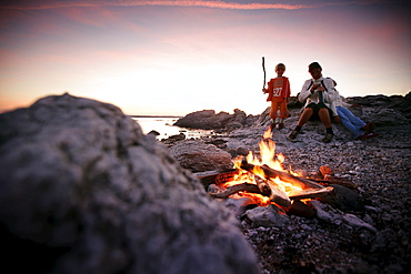 Mother with two children on beach near camp fire at sunset, Sysne, Gotland, Sweden