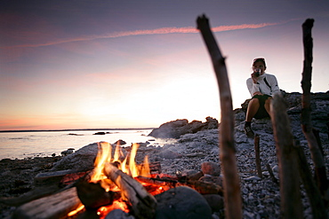 Woman drinking wine near a log fire on the beach at sunset, Sysne, Gotland, Sweden