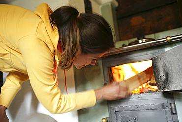 Woman heating in a alp lodge, Heiligenblut, Hohe Tauern National Park, Carinthia, Austria