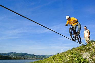 Trial biker on steel rope at Danube River, Linz