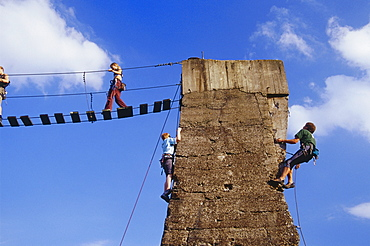 Climbers climbing up a tower at Huette Meiderich, Public Park in Duisburg North, Duisburg, Ruhr Valley, North Rhine Westphalia, Germany