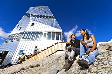 Two young people with headphones in front of New Monte Rosa Hut, myclimate audio trail, Zermatt, Pennine Alps, Canton of Valais, Switzerland