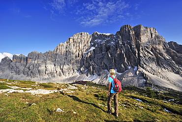Woman walking towards Rifugio Tissi, Civetta in the background, Civetta, Dolomites, UNESCO World Heritage Site, South Tyrol, Italy