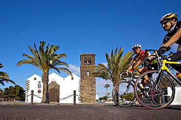Cyclist passes the Church Iglesia Nuestra Senora de Candelaria, La Olvia, Fuerteventura, Canary Islands, Spain