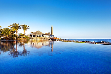 Pool of the Grand Hotel Costa and lighthouse under blue sky, Meloneras, Maspalomas, Gran Canaria, Canary Islands, Spain, Europe