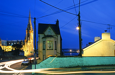 Calm street setting and the illuminated St. Colman's cathedral in the evening, Cobh, County Cork, Ireland, Europe