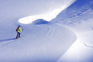 Woman backcountry skiing crossing a snowface, Nadernachjoch Skitour, Neue Bamberger hut, Kitzbuehel Alps, Tyrol, Austria