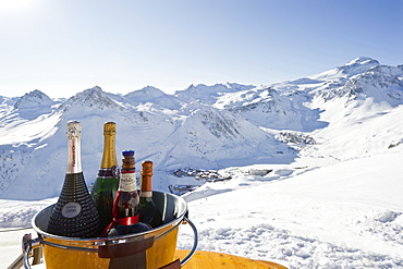 Bottles of champagne in a cooler, Snow-capped mountains in the background, Tignes, Val d Isere, Savoie department, Rhone-Alpes, France