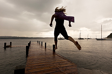 Young woman jumping over pier, high water at Lake Starnberg, Upper Bavaria, Germany, Europe