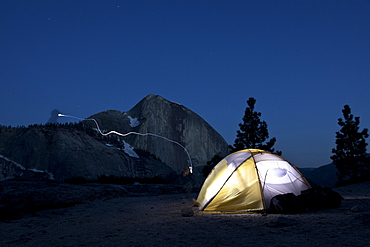 Headlamp amd lit tent in front of Half Dome at night, Yosemite National Park, California, USA, America