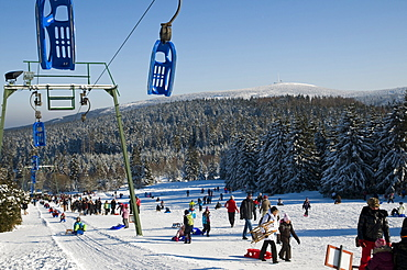 Children sledging, Sledge lift, sledge hill Torfhaus, Brocken in background, Altenau, Harz, Lower Saxony, Germany