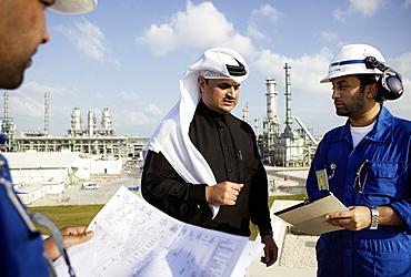 Men having a meeting, refinery in background, Ras Laffan Industrial City, Qatar