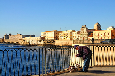 Angler with the houses of Siracusa in the background, at Lungomare, Siracusa