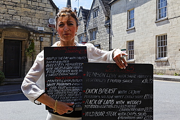 Woman showing the menu of the The Royal Oak Pub, Painswick, Gloucestershire, Cotswolds, England, Great Britain, Europe